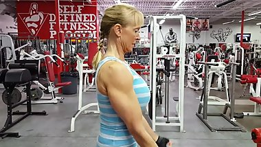Old woman with large breasts and muscular arms trains biceps