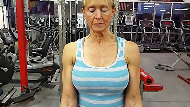 old woman with large breasts and muscular arms trains biceps 2